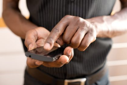 Torso shot of a man's hands tapping a black smartphone